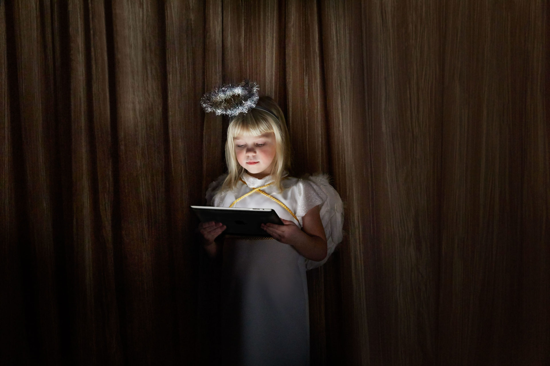 – Shaw & Shaw Photography – Shaw and Shaw Photographers Manchester – advertising photographers – graphic image – Nativity Angel – girl dressed as an angel looking at an iPad – Christmas play – Nativity play