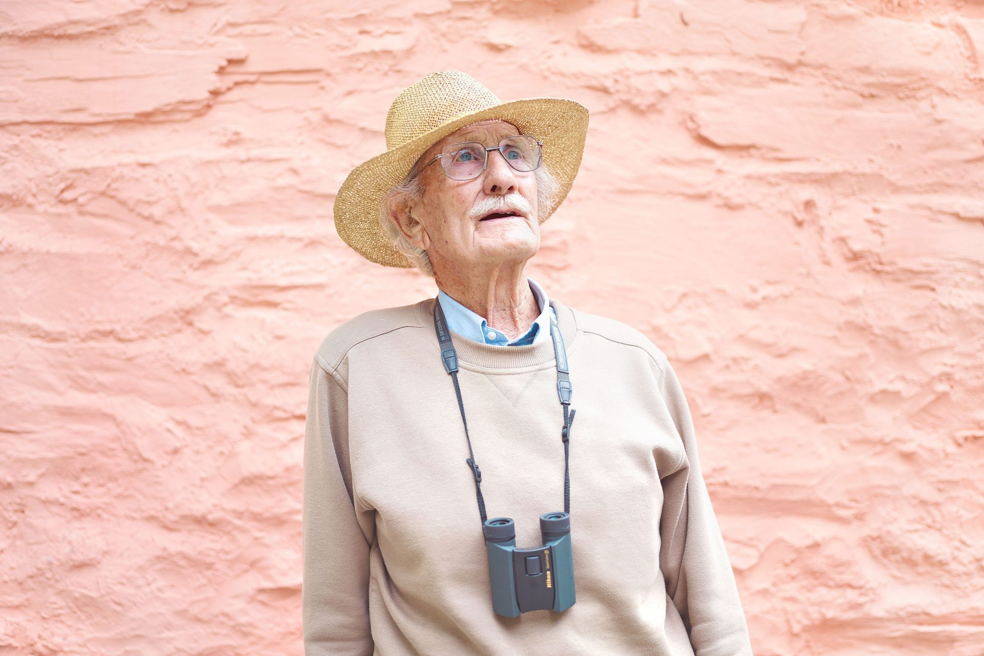 old man in straw hat day tripper with binoculars pink wall  – Shaw and Shaw Advertising photographers Manchester photographer – Shaw & Shaw Photography – Skiddle