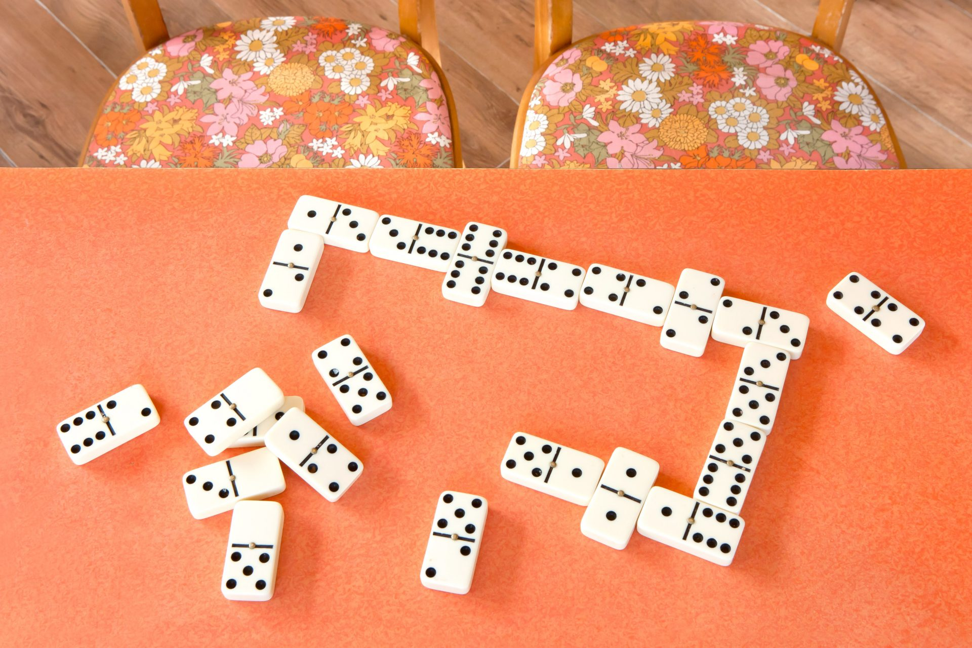 Shaw & Shaw – Dominoes on an orange table vintage chairs – Shaw and Shaw Advertising photographers Manchester photographer graphic image