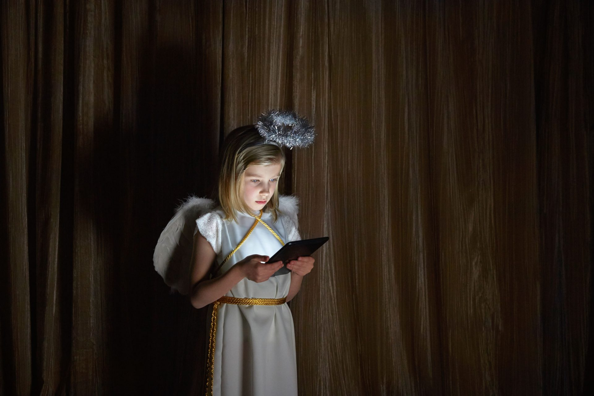 – Shaw & Shaw Photography – Shaw and Shaw Photographers Manchester – advertising photographers – graphic image – Angel – girl dressed as an angel looking at an iPad – Christmas play – Nativity play