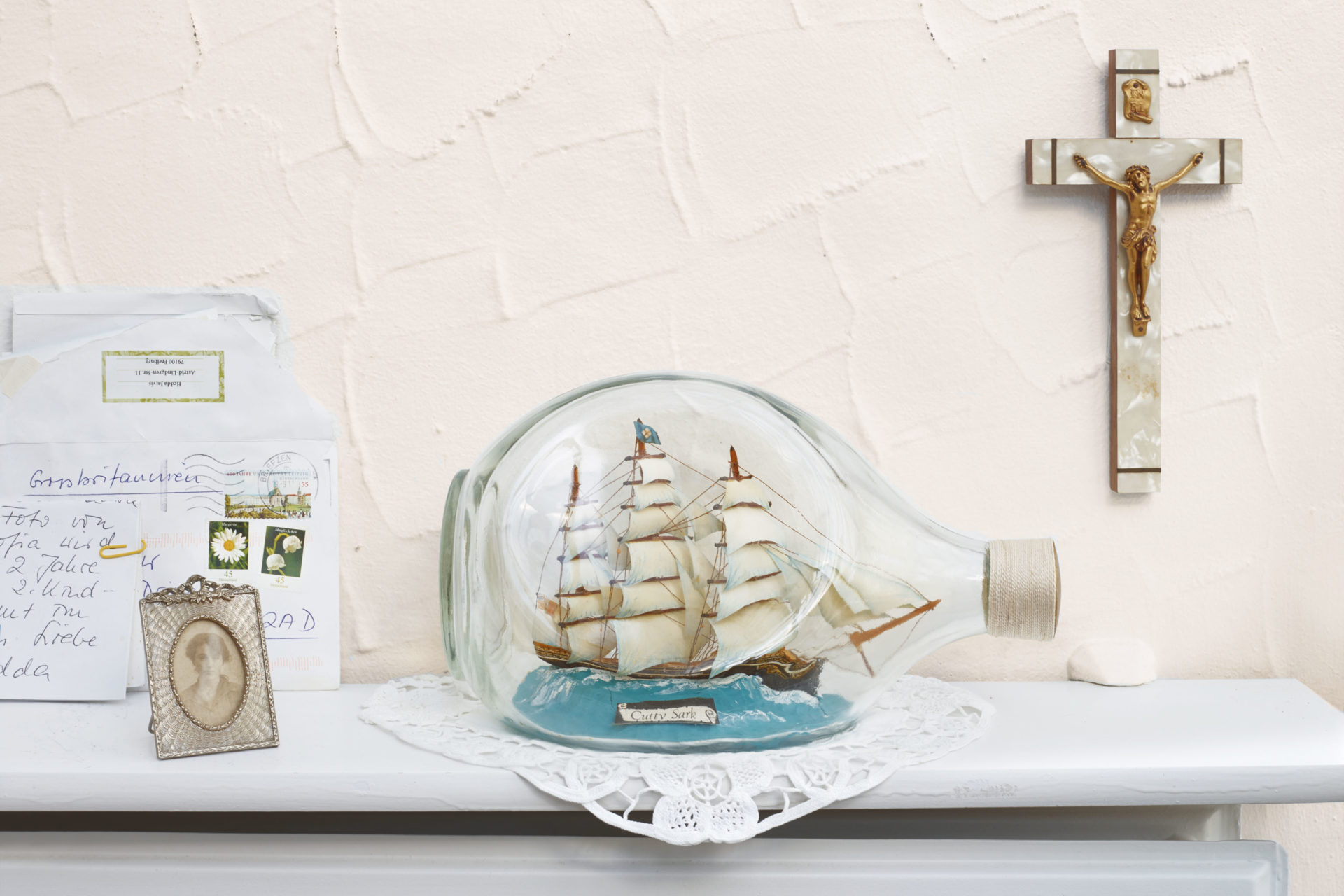 Ship in a bottle on a shelf with crucifix – Shaw & Shaw Photography campaign – Shaw and Shaw advertising photographers